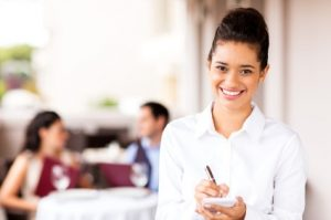 Portrait of beautiful waitress holding order pad and pen with couple in background at restaurant. Horizontal shot.